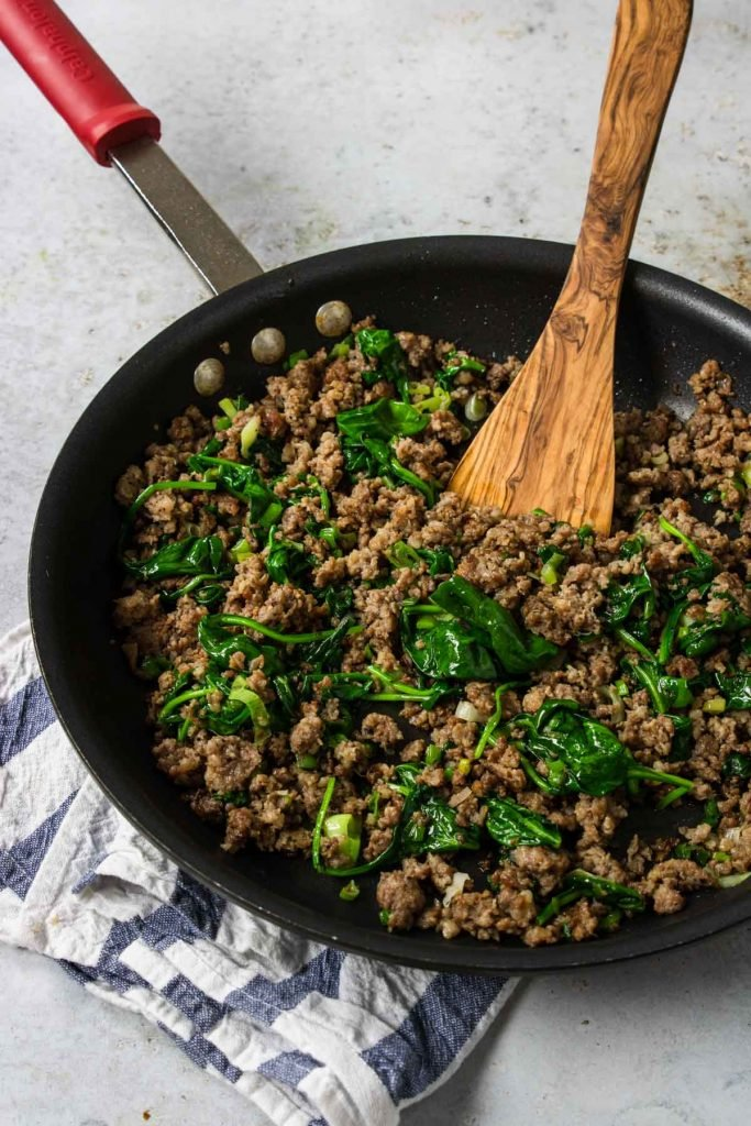 crumbled breakfast sausage with spinach and basil in a skillet