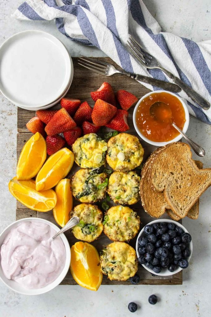 a breakfast board with sausage egg cups, fruit, yogurt and toast