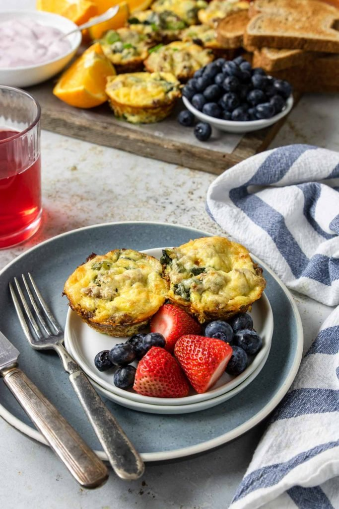 sausage egg cups on a plate with fresh fruit