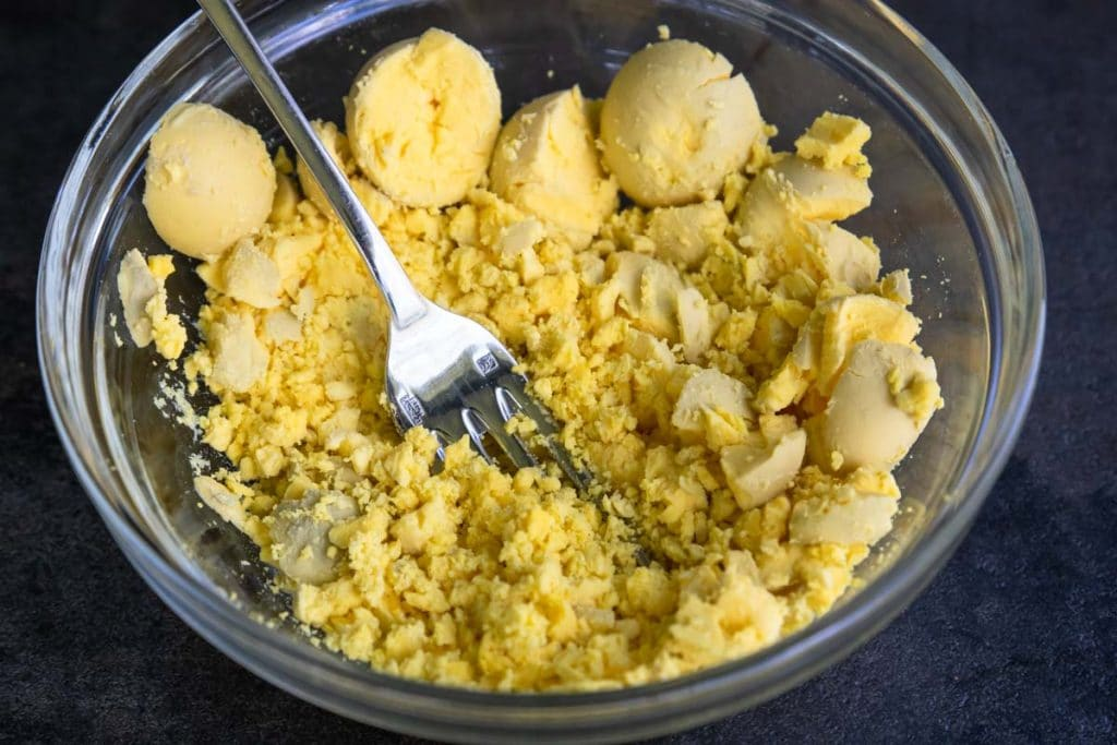 Cooked egg yolks being crumbled with a fork