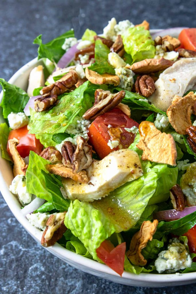 Apple Pecan Chicken Salad in a white bowl topped with chicken tomatoes apple chips red onions and blue cheese