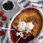Berry cobbler with vanilla cake like topping and topped with two scoops of vanilla ice cream