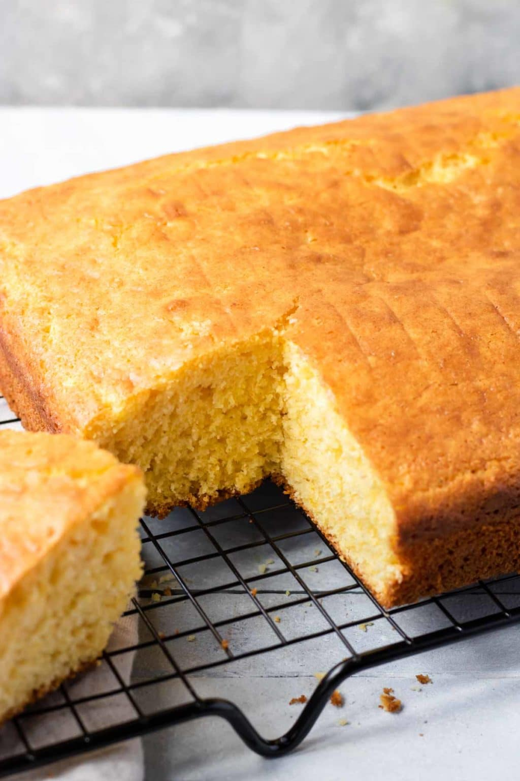 Cornbread made with a box of yellow cake mix and two jiffy corn muffin mixes, cooling on a black cooling rack