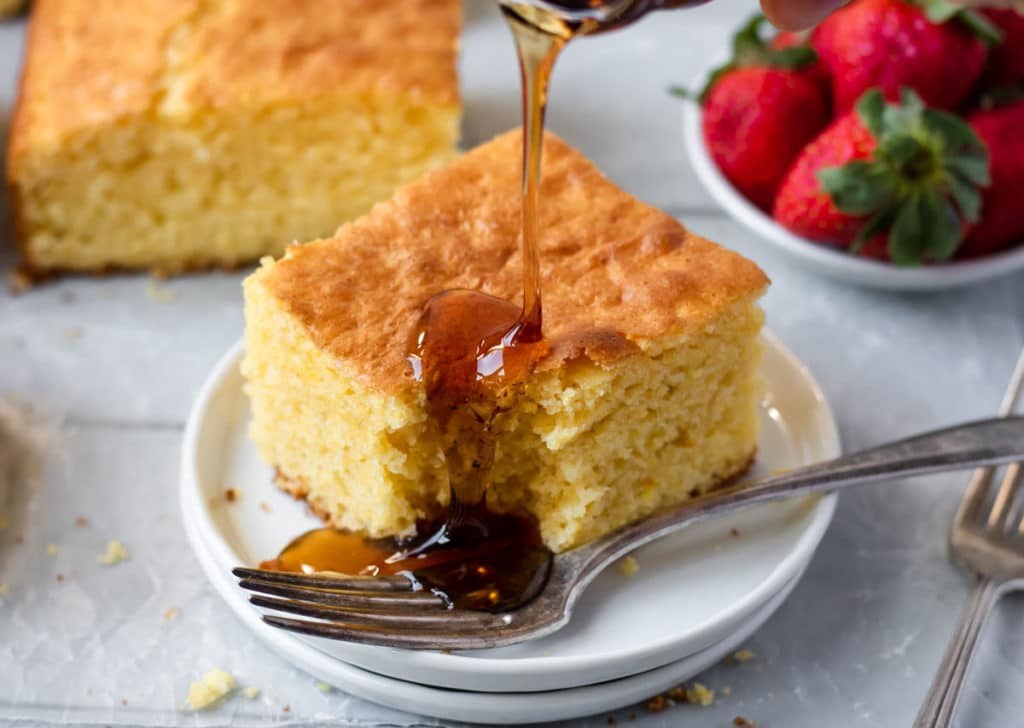 a piece of best ever cornbread on a white plate being drizzled with syrup