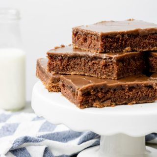Chocolate sheet cake cut into squares and placed on a cake pedestal