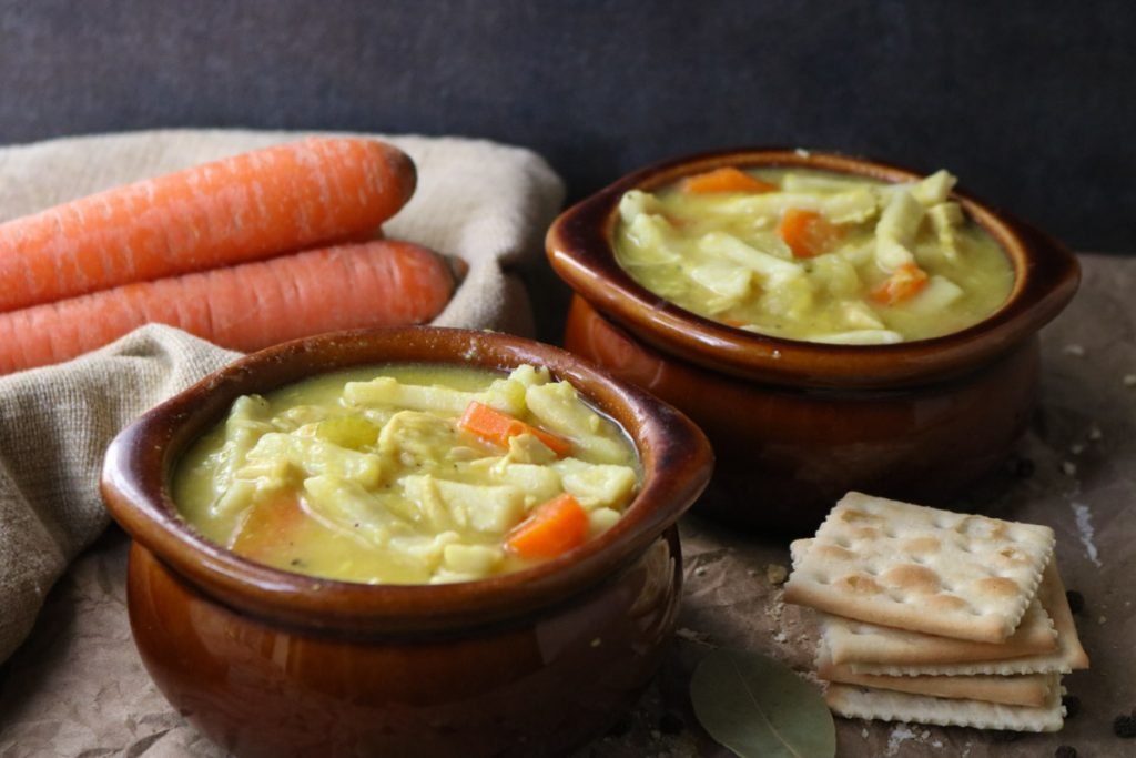 Two bowls of Homemade Chicken Noodle Soup with saltine crackers to the side and carrots in the background momsdinner,net