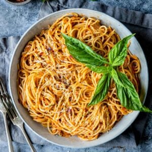 pasta with roasted red pepper sauce garnished with fresh basil
