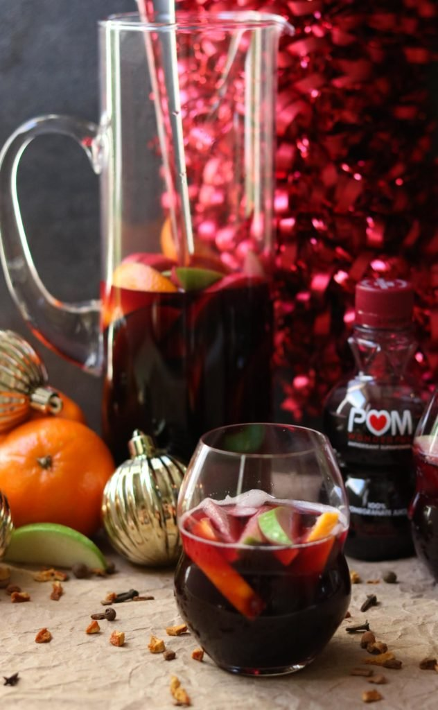 A glass and a pitcher of red wine Winter Sangria mixed with fruit, and a bottle of POM Pomegranate juice momsdinner.net