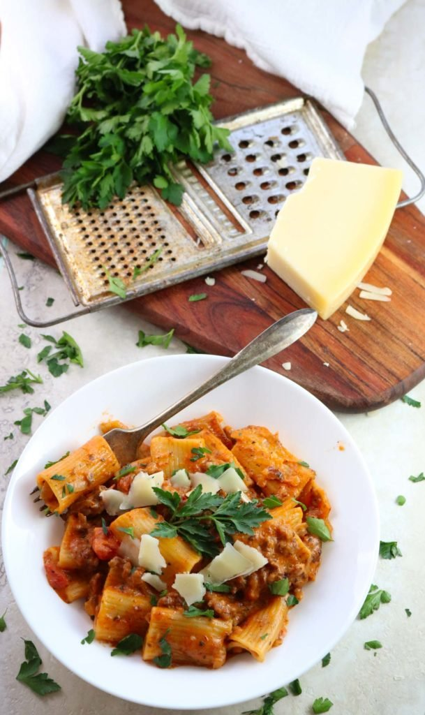 Instant Pot Sausage Rigatoni with tomato cream sauce in a bowl with parsley and parmesan