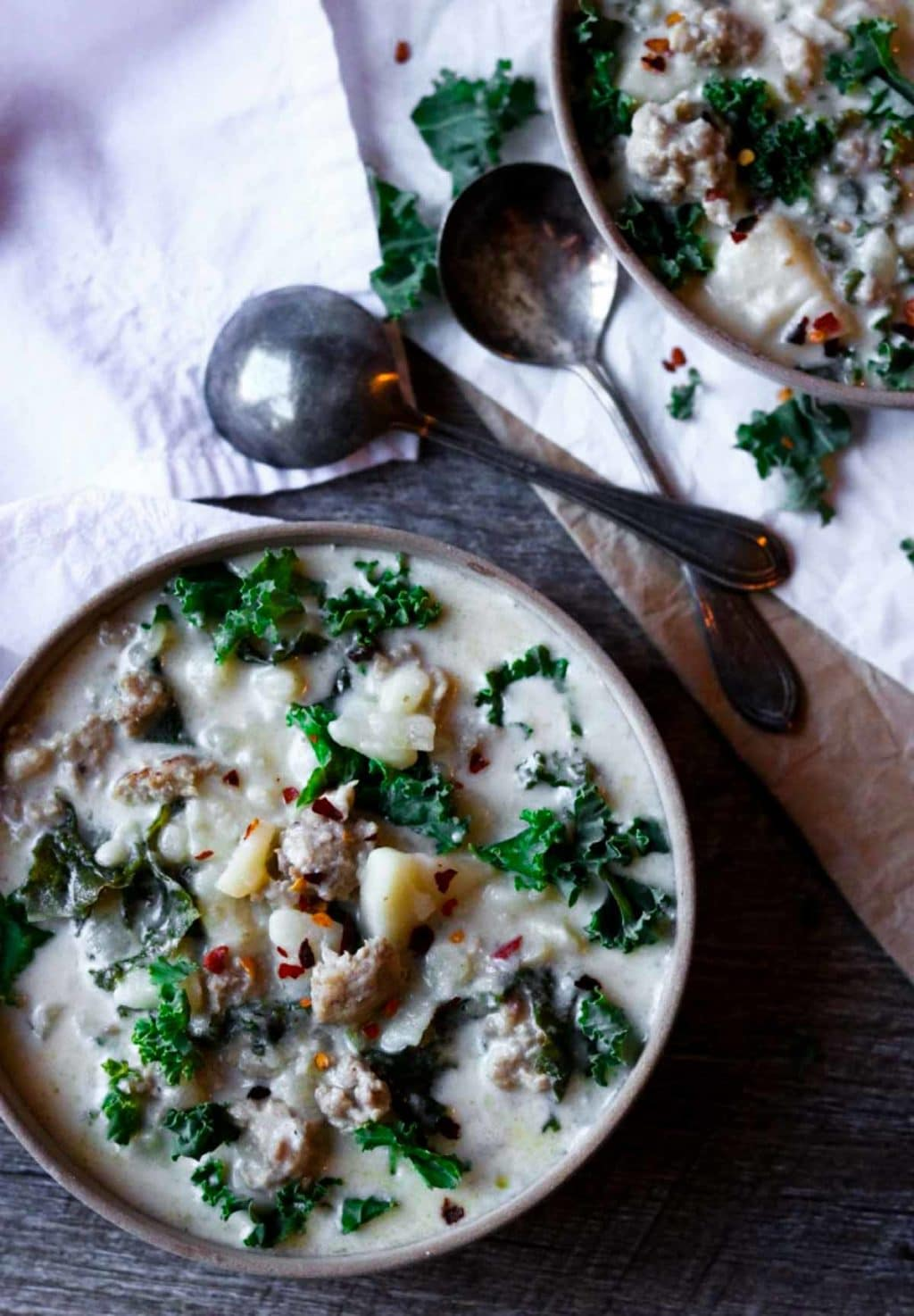Two bowls of Instant Pot Zuppa Toscana with two spoons in the middle