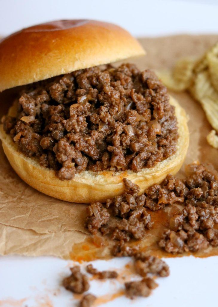 Homemade Sloppy Joe Sandwich with the bun tilted to the side and the ground beef mixture spilling over the front