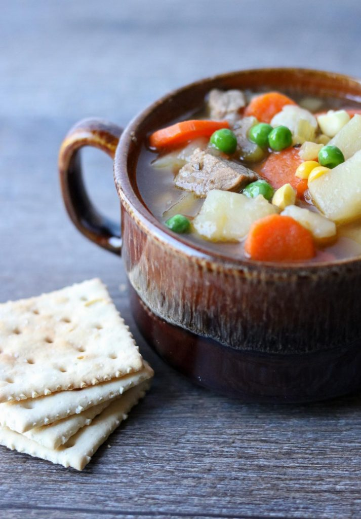Instant Pot Steak Soup in a brown mug with a stack of saltine crackers to the side