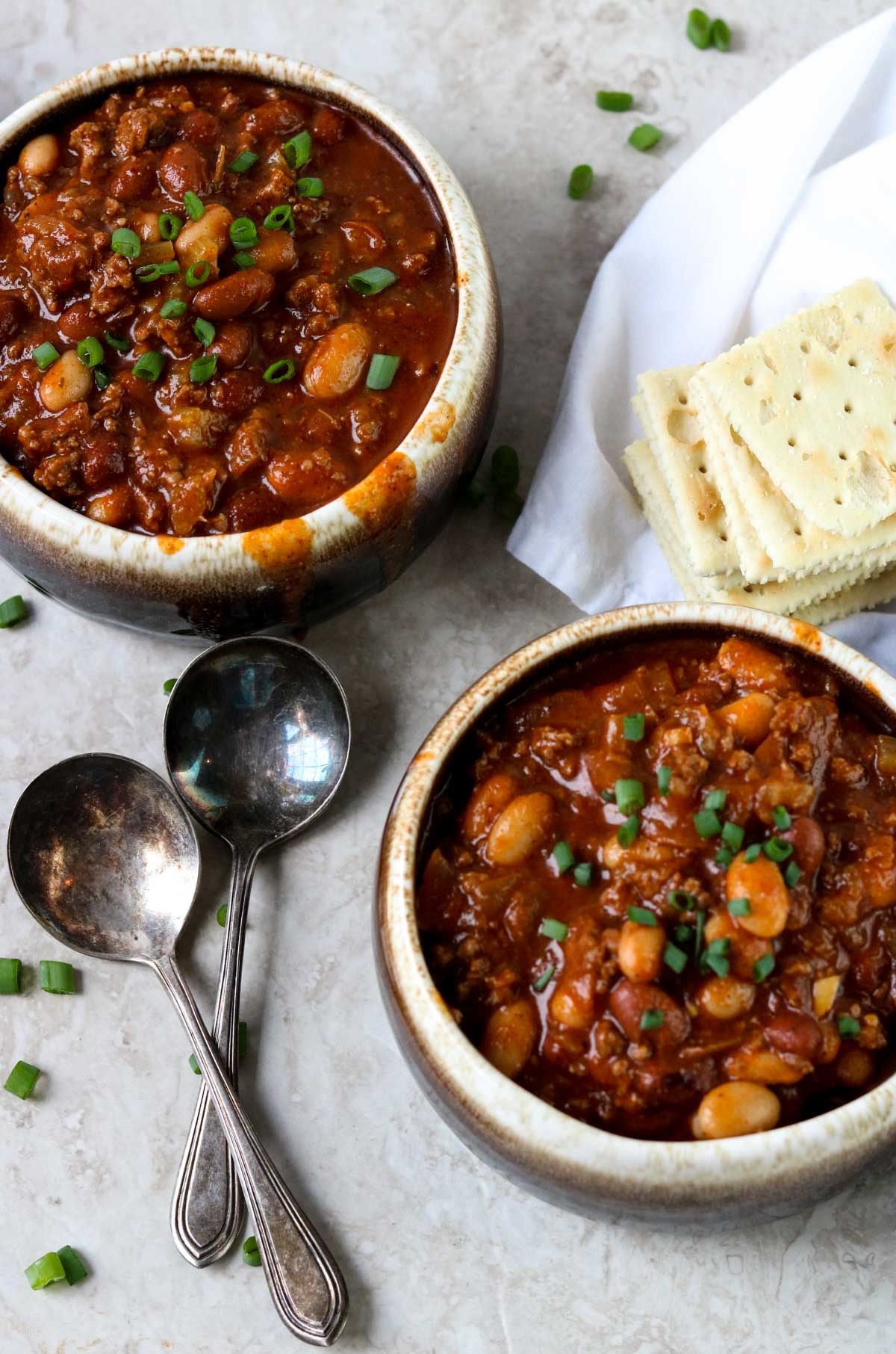 Two bowls of Classic Chili with crackers and spoons