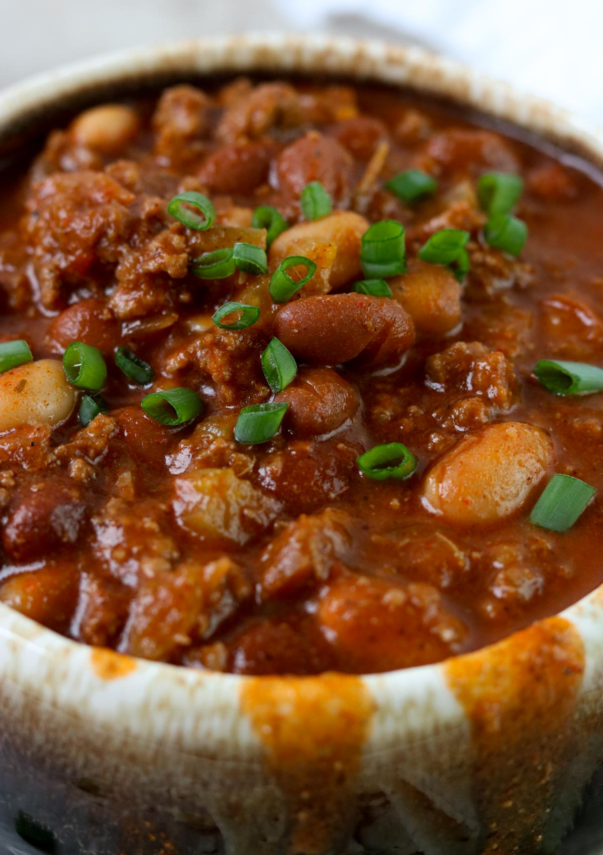 Up close picture of thick chili with beans and tomatoes topped with green onions