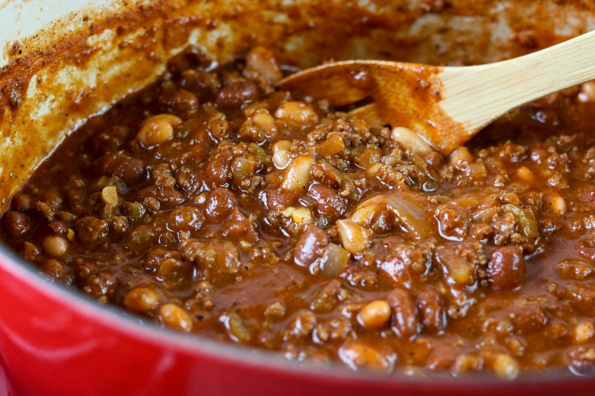 chili in a pot with a wooden spoon