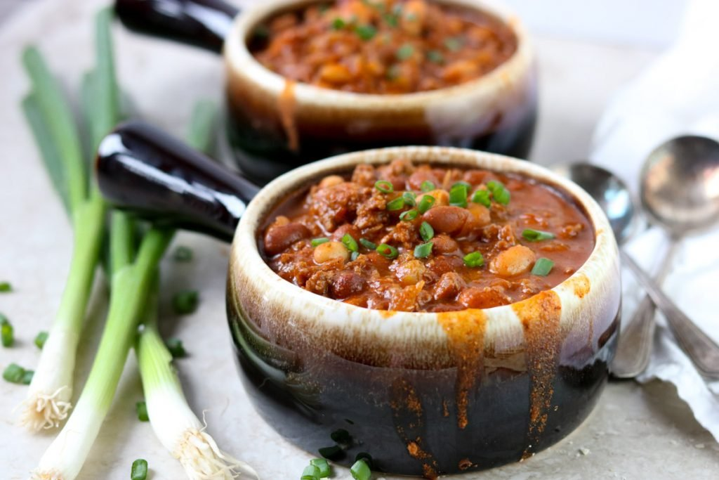 two bowls of classic chili and green onions to the side