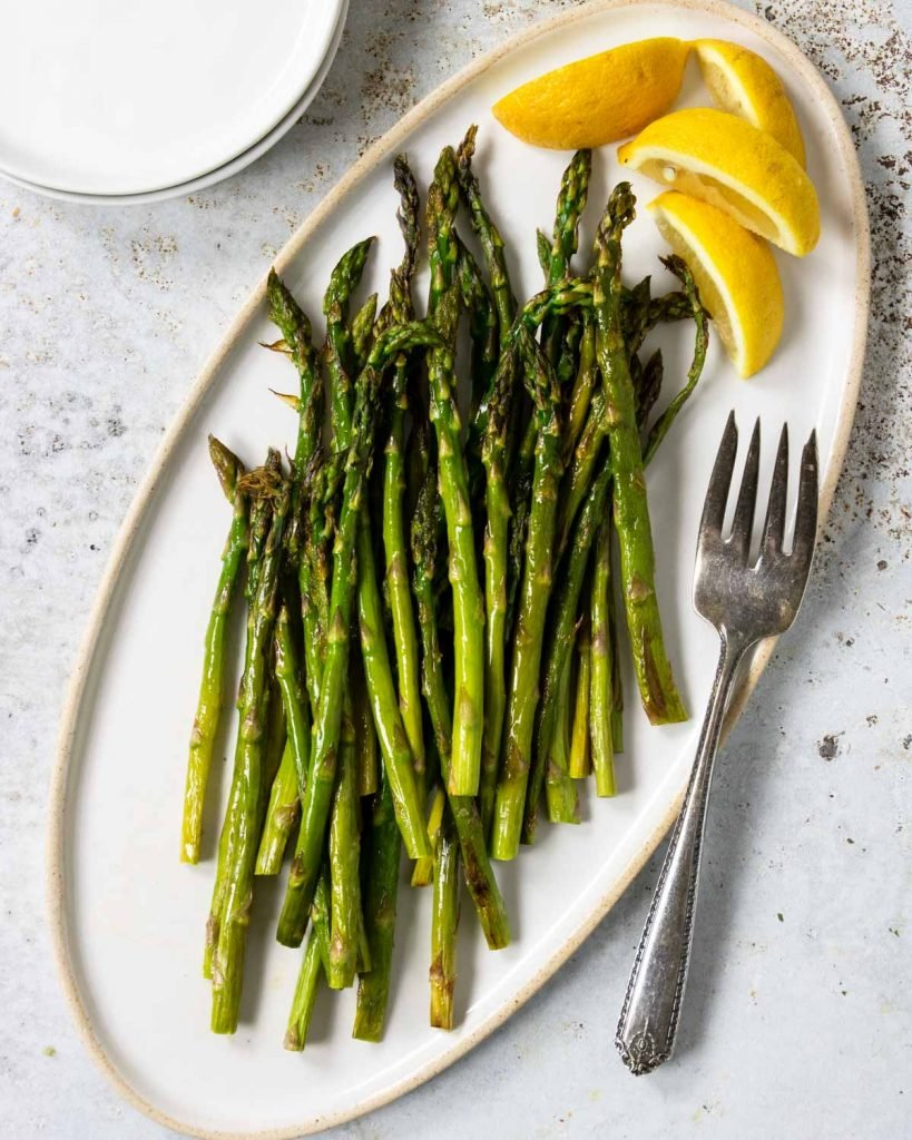 Oven Roasted Asparagus on a white plate with lemon wedges