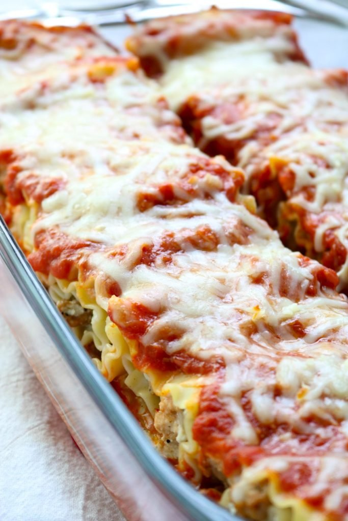 A glass baking dish full of lasagna roll ups after they are baked www.momsdinner.net