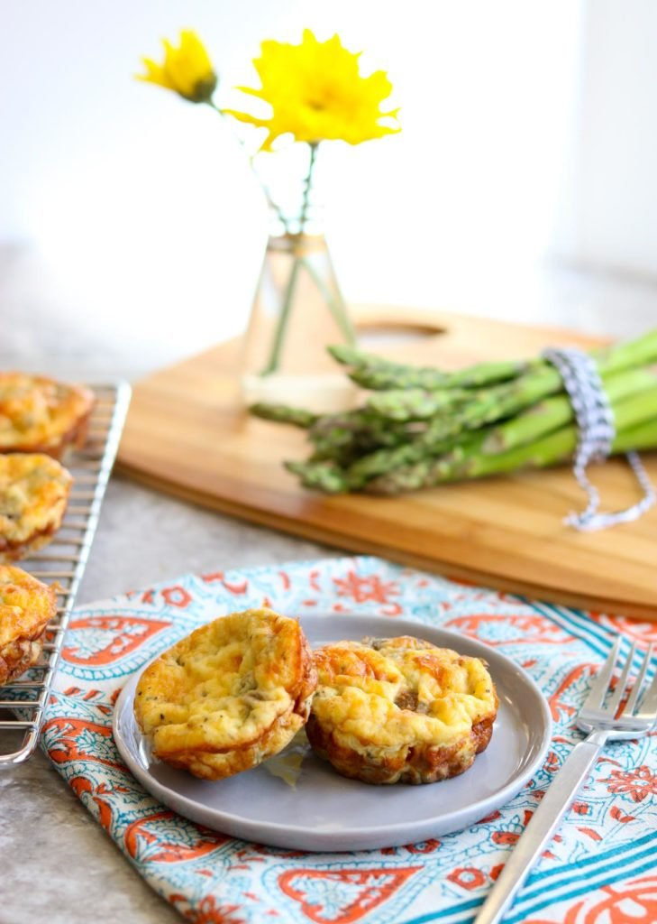 a plate with two egg cups and asparagus in the background