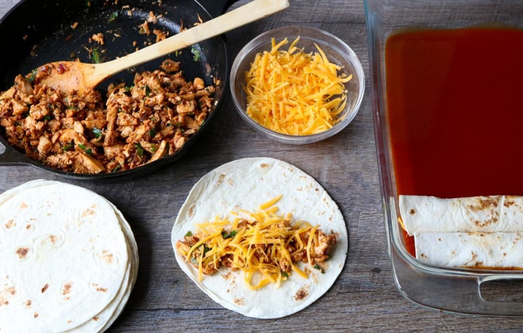 Chicken Enchilada assembly line: flour tortillas, chicken enchilada filling, cheese, baking pan with enchilada sauce momsdinner.net