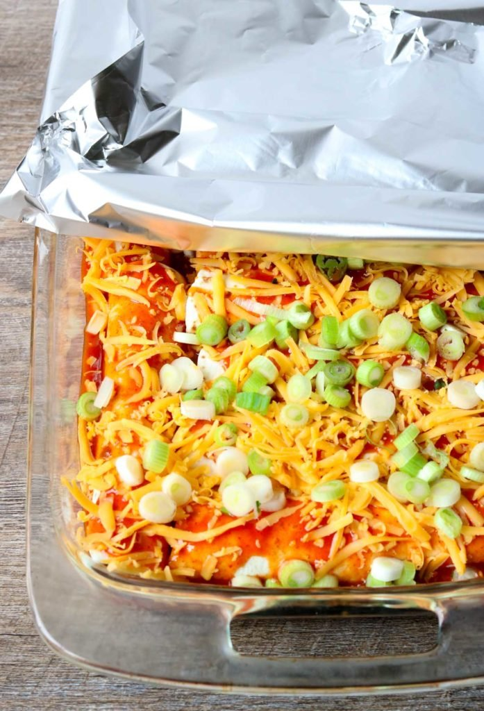 Chicken Enchilada in a glass baking dish before they are baked, foil rolled back on the top momsdinner.net