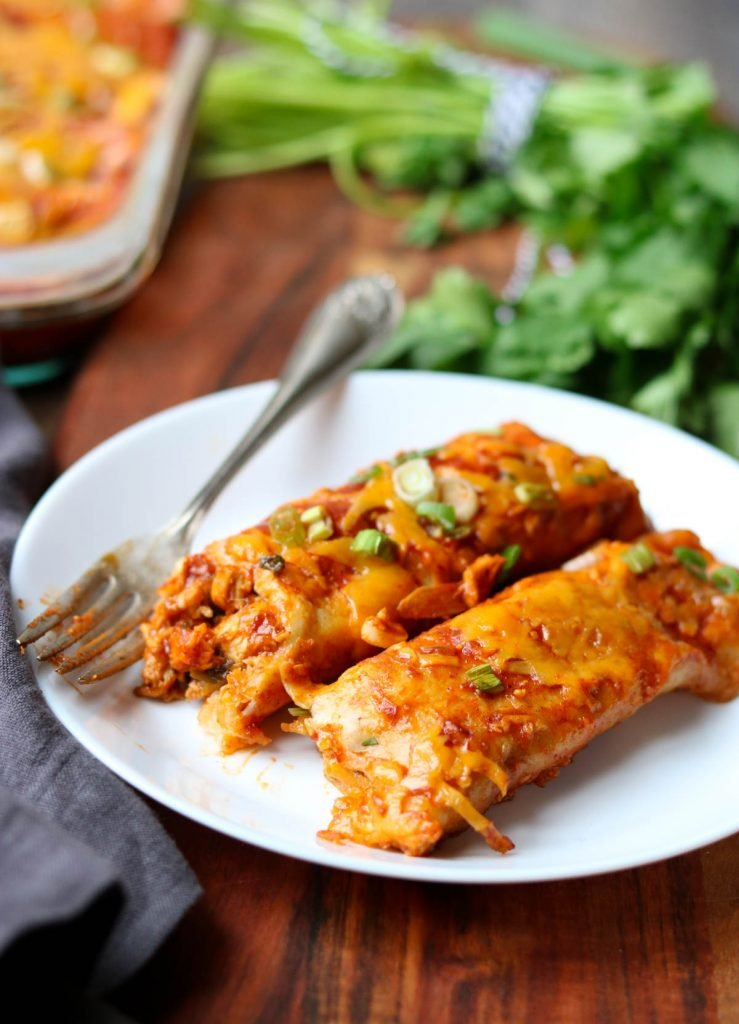 2 Chicken Enchiladas on a white plate with a fork, cilantro in the background momsdinner.net