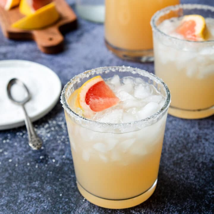 a glass of grapefruit margarita with a salty plate in the background