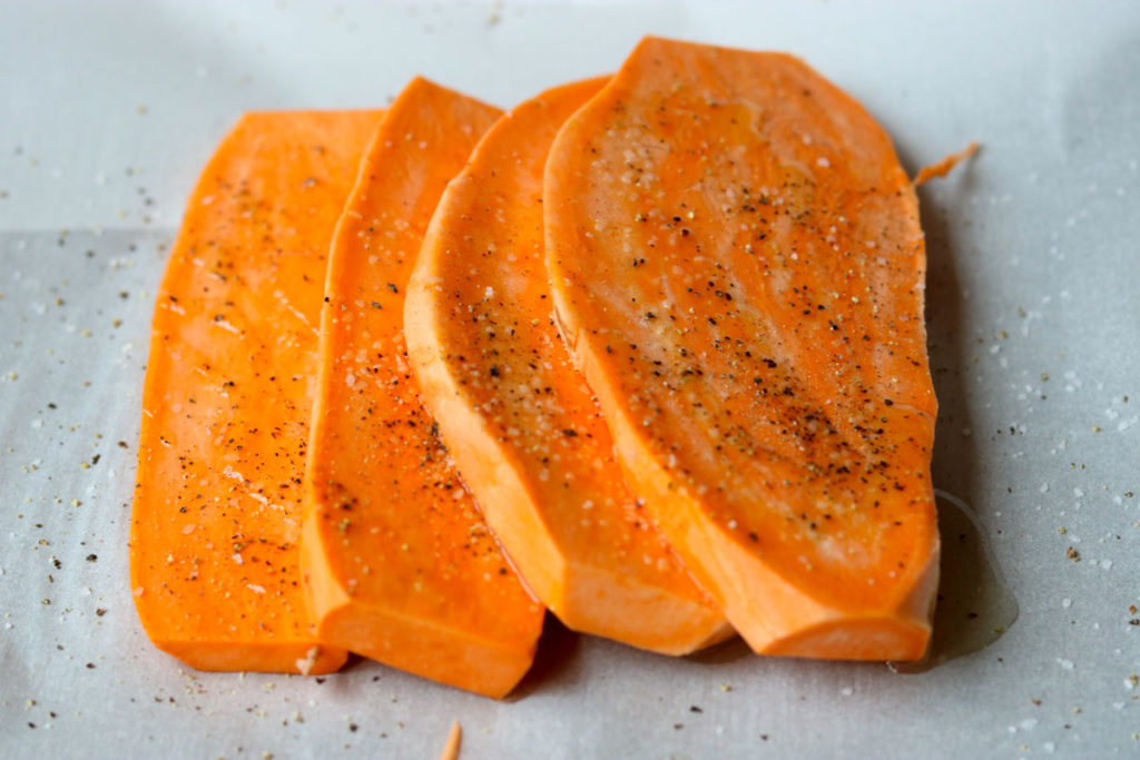 Fresh cut sweet potatoes on parchment with salt and pepper