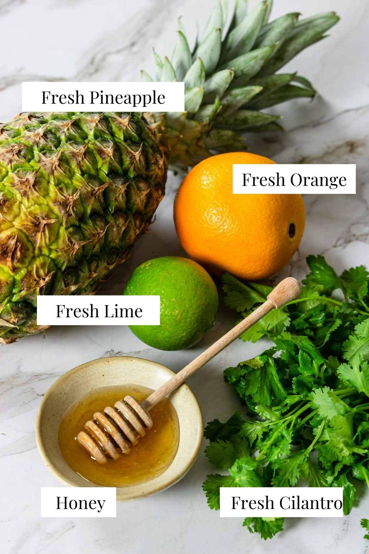 pineapple, orange, lime, honey and cilantro on a table