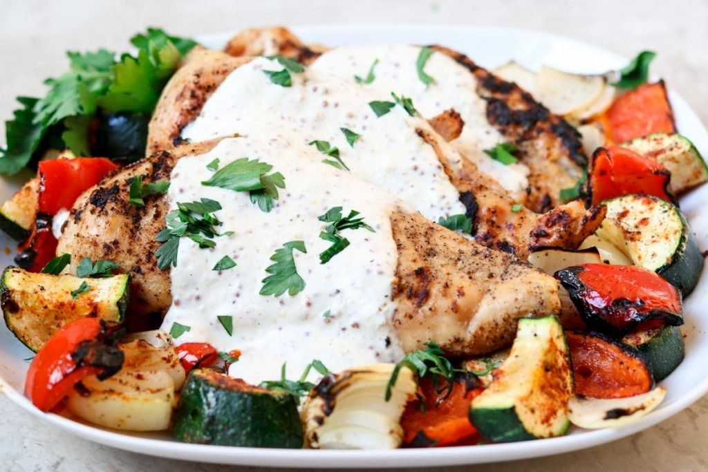 a plate of grilled veggies and chicken topped with cream sauce