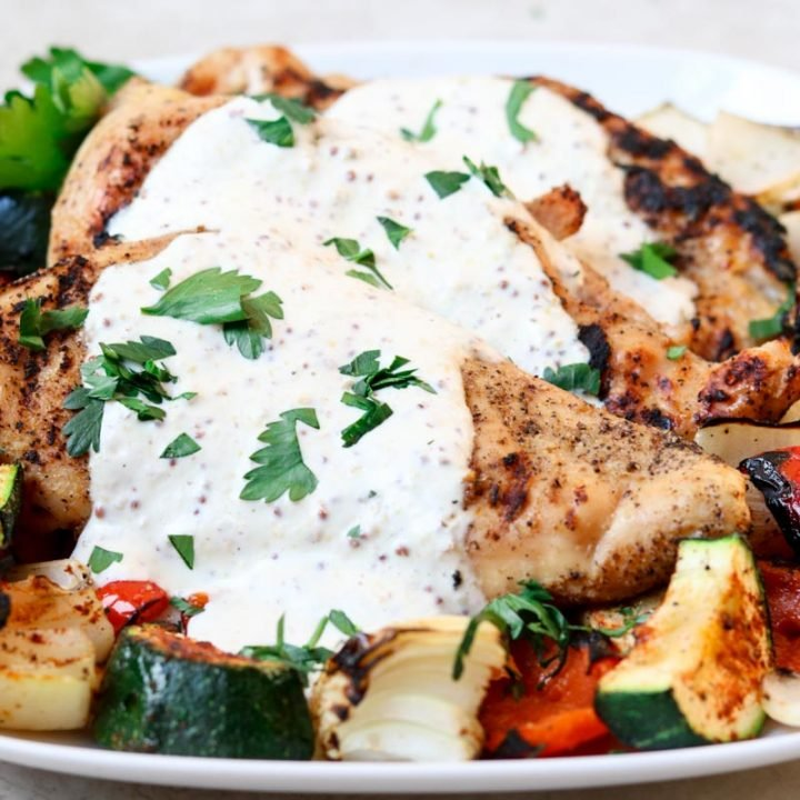 grilled chicken topped with cream sauce and grilled veggies