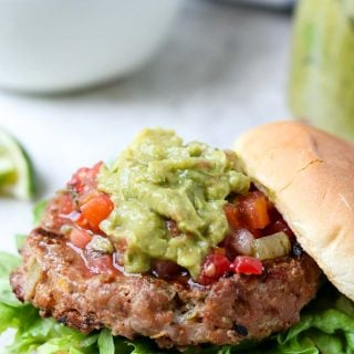 a close up of a juicy turkey burger with guacamole