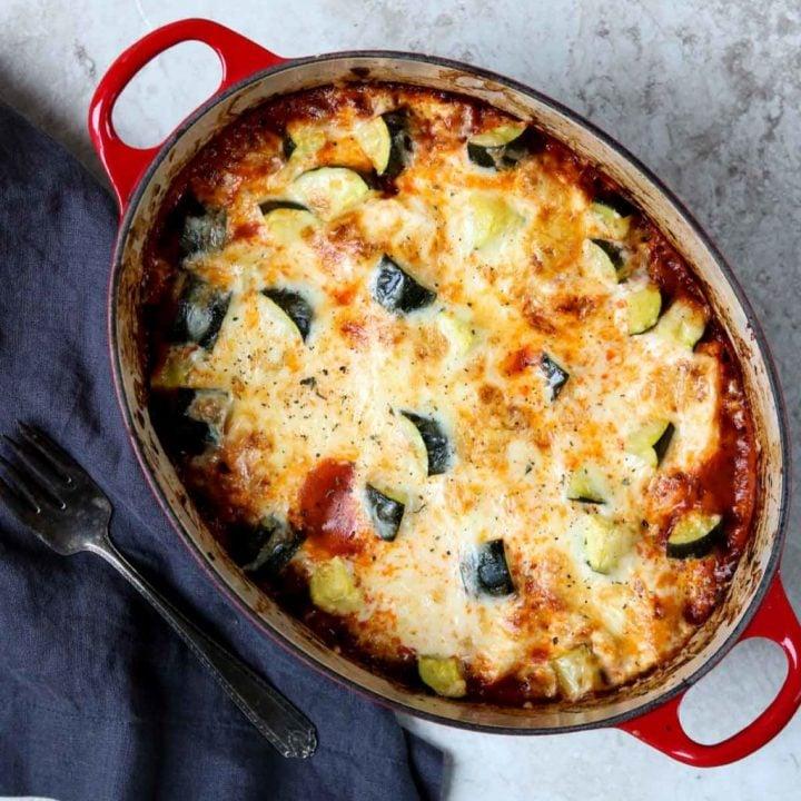 a red dutch oven full of lasagna