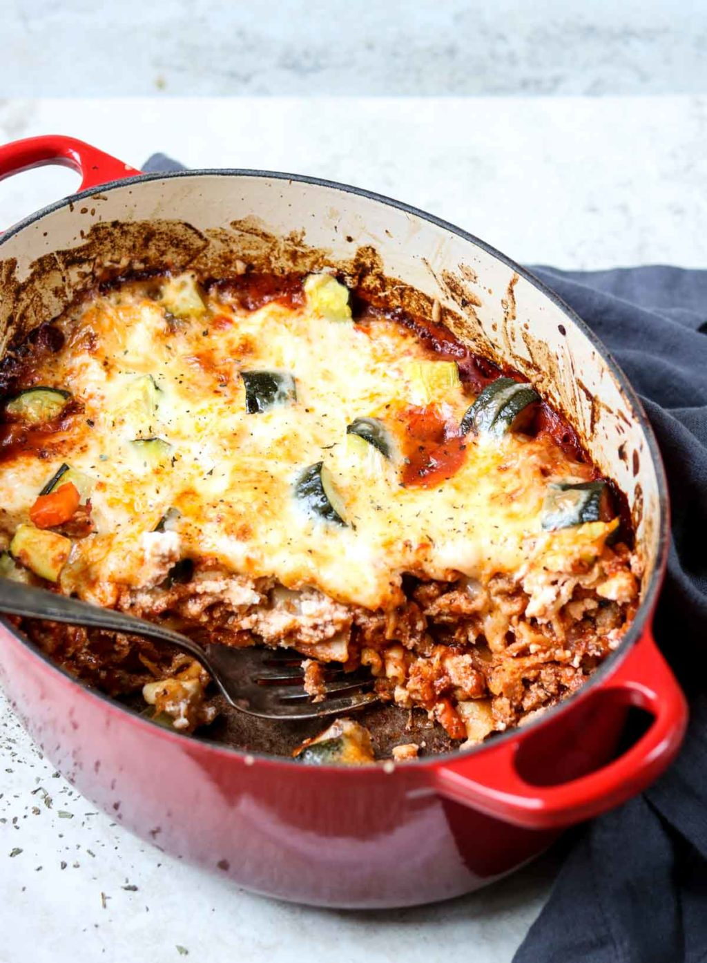 Dutch Oven Lasagna in a red Le Creuset with a scoop taken out