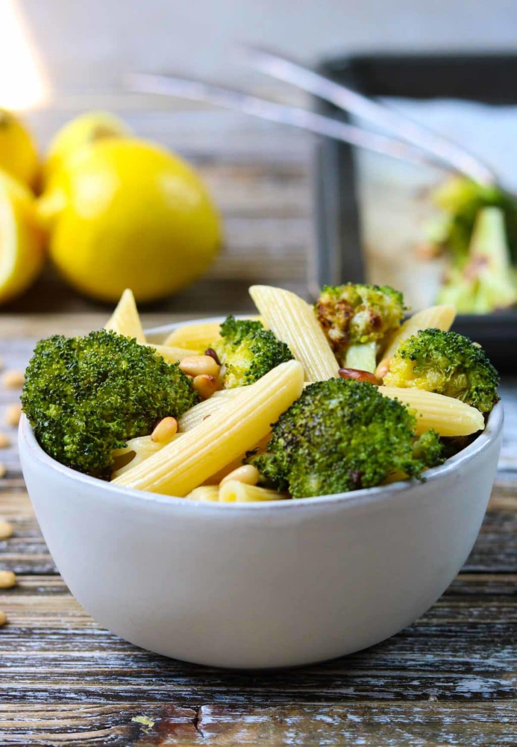 A white bowl full of pasta and broccoli, lemons in the background
