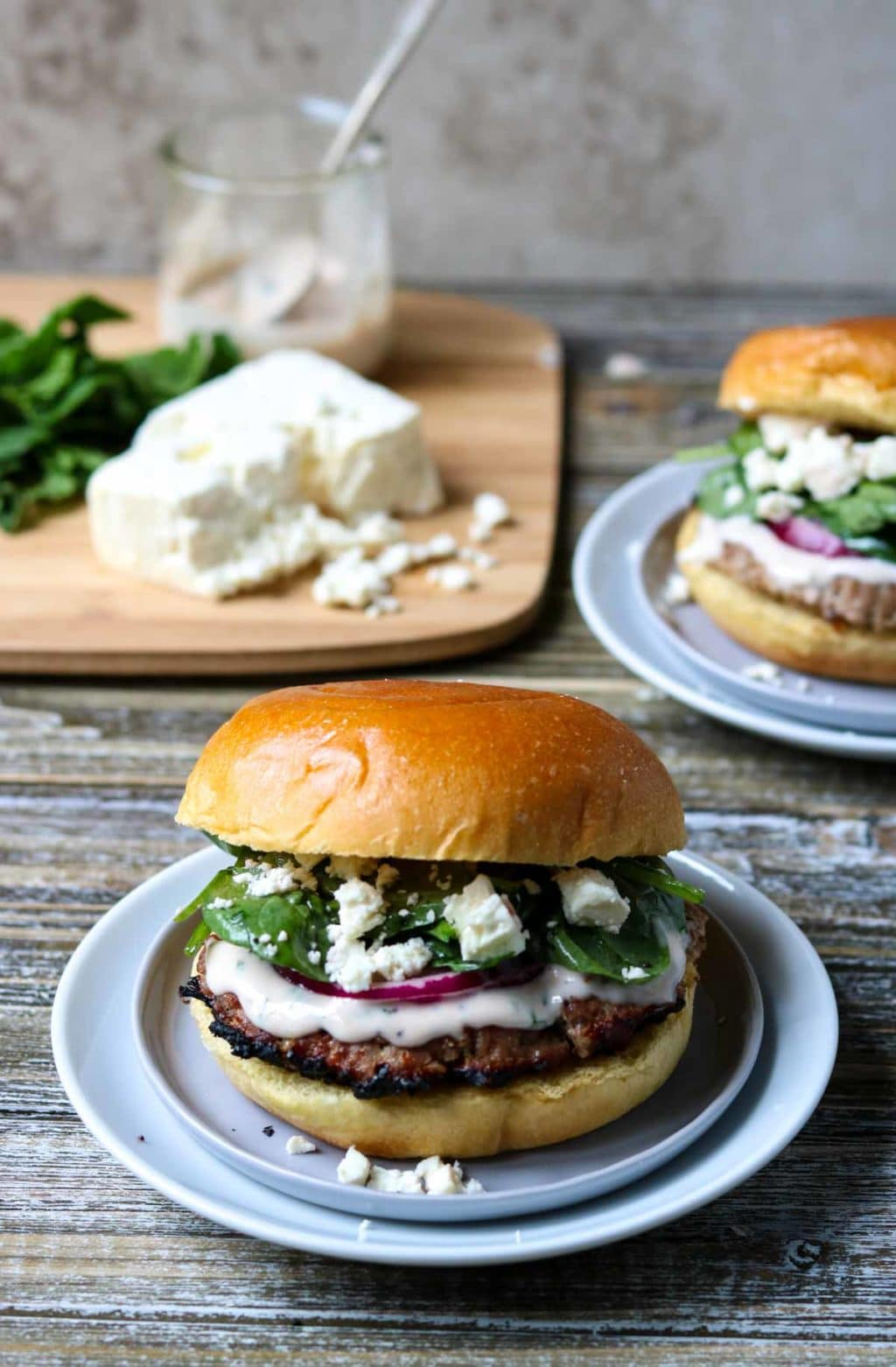Two Greek Turkey Burgers with a cutting board in the back with feta cheese, spinach and raspberry mint aioli on it