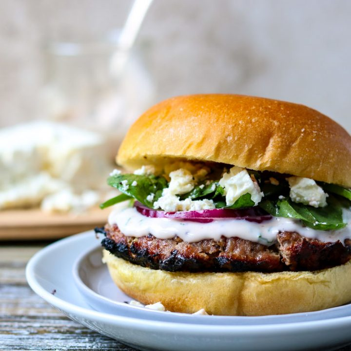 greek turkey burger on a plate topped with feta cheese and spinach