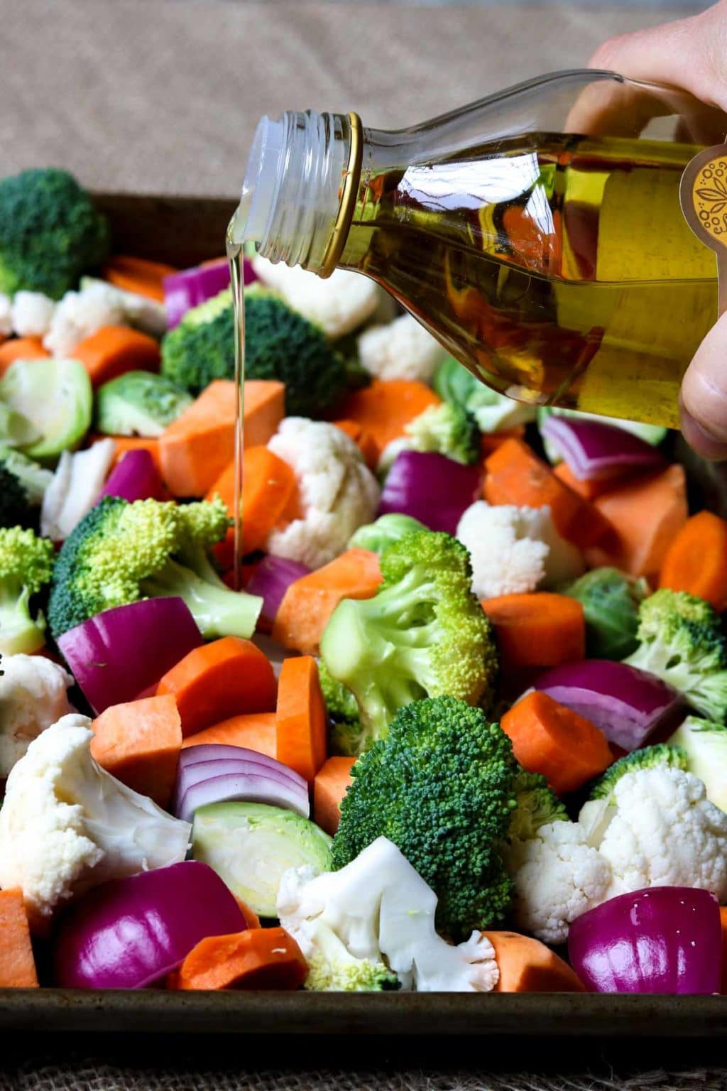 Olive oil being drizzled on cut veggies on a sheet pan