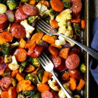 Healthy Sheet Pan Dinner with carrots, sweet potatoes, sausage, brussels, and drizzled with a smoked paprika vinaigrette
