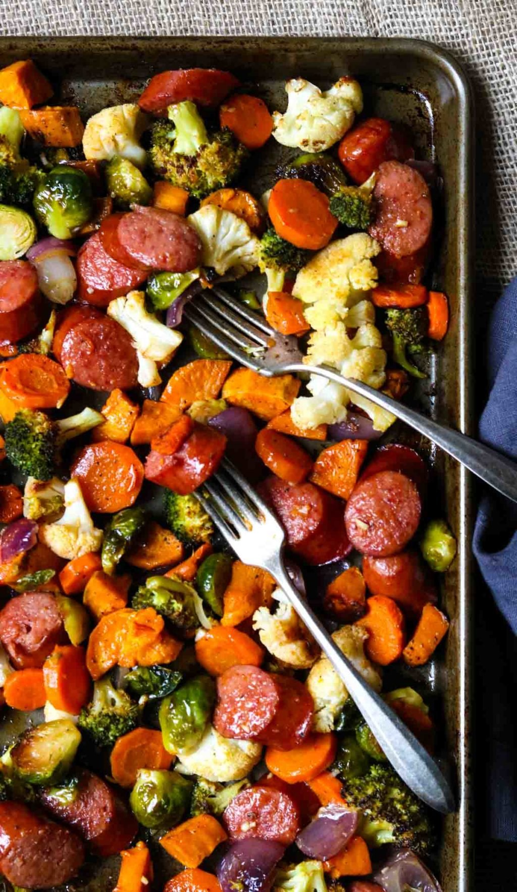 A sheet pan with two forks, full of roasted cauliflower, broccoli, brussle sprouts, carrots, sweet potatoes, and sausage