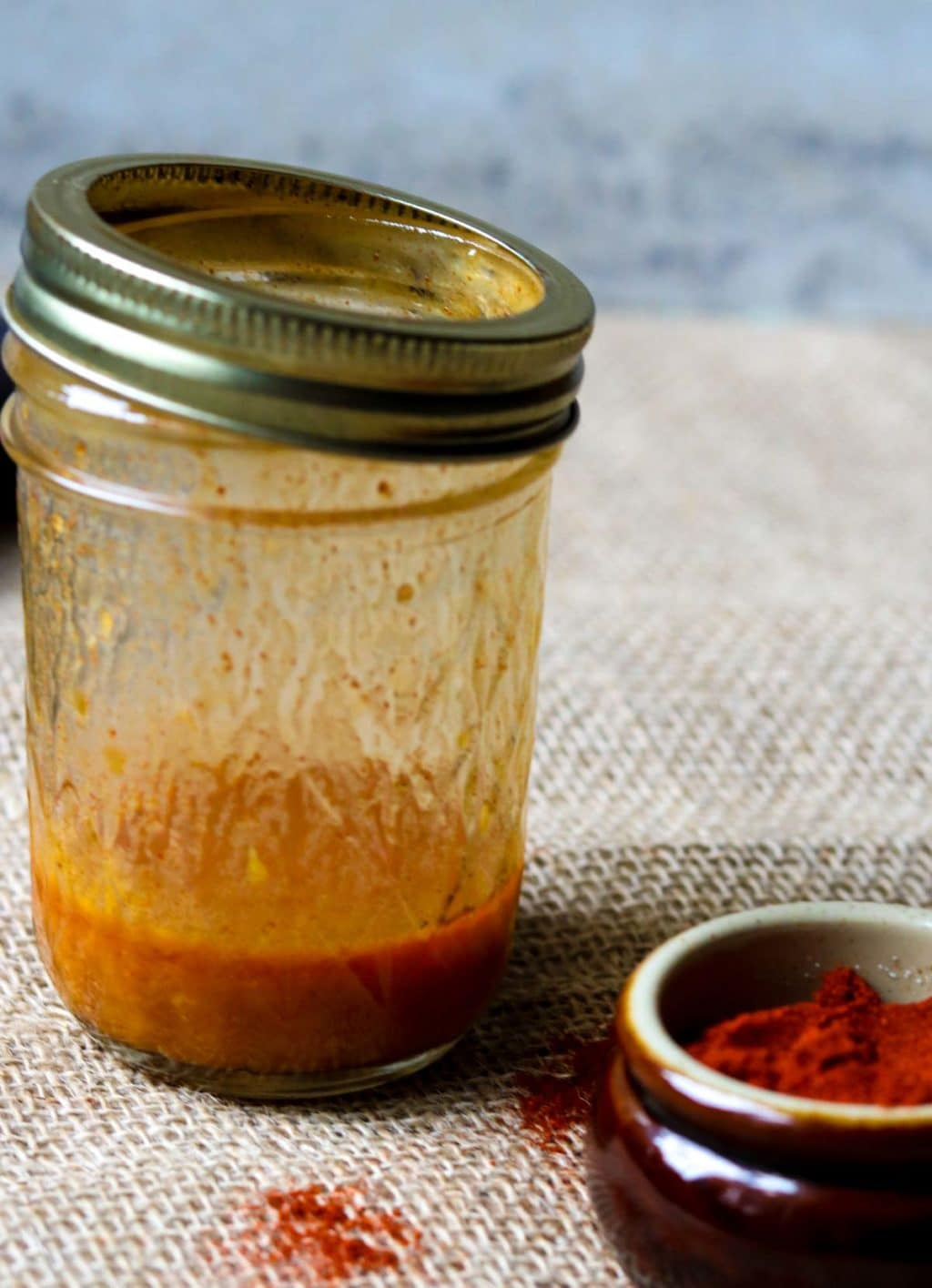Smoked Paprika Vinaigrette in a mason jar with a bowl of smoked paprika to the side