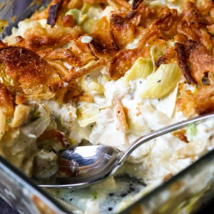 creamy artichoke chicken salad in a baking dish topped with french fried onions