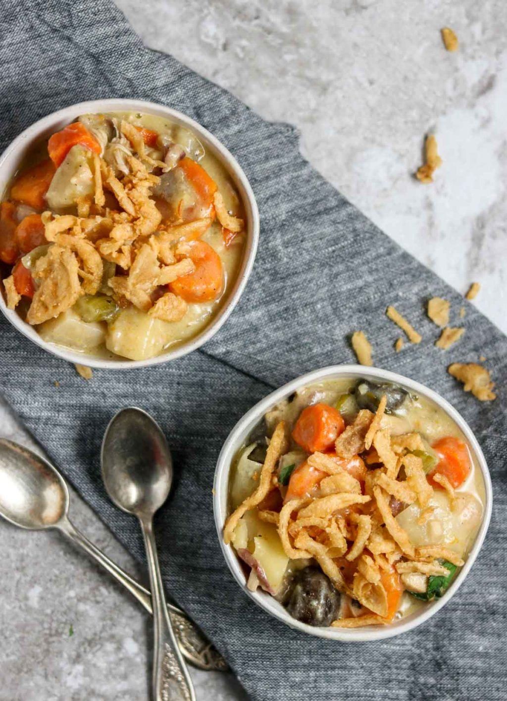 two white bowls of chicken pot roast garnished with french fried onions, sitting on a grey towel with two spoons