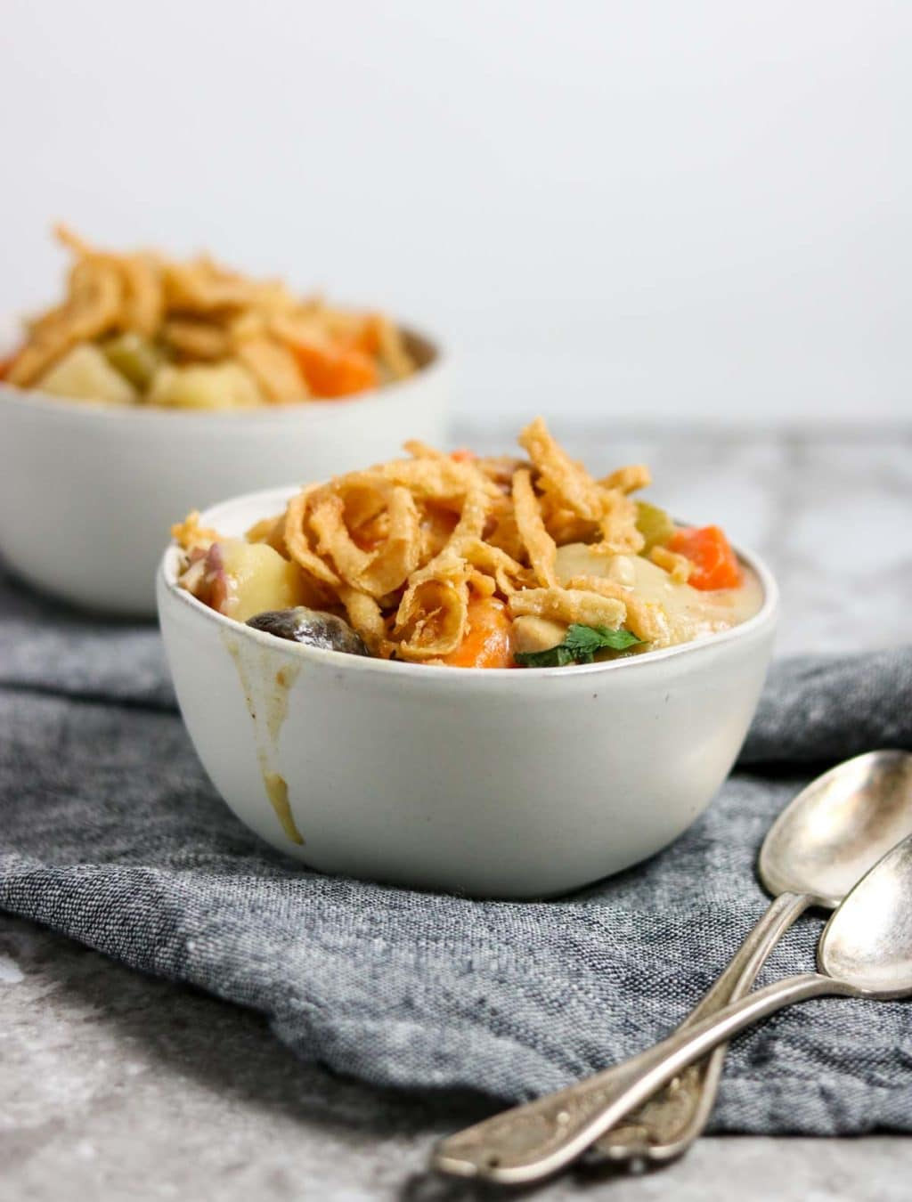 two bowls of chicken pot roast garnished with french fried onions and two spoons to the side