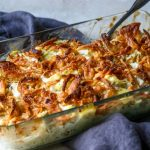 hot artichoke chicken salad topped with french fried onions in a glass casserole dish