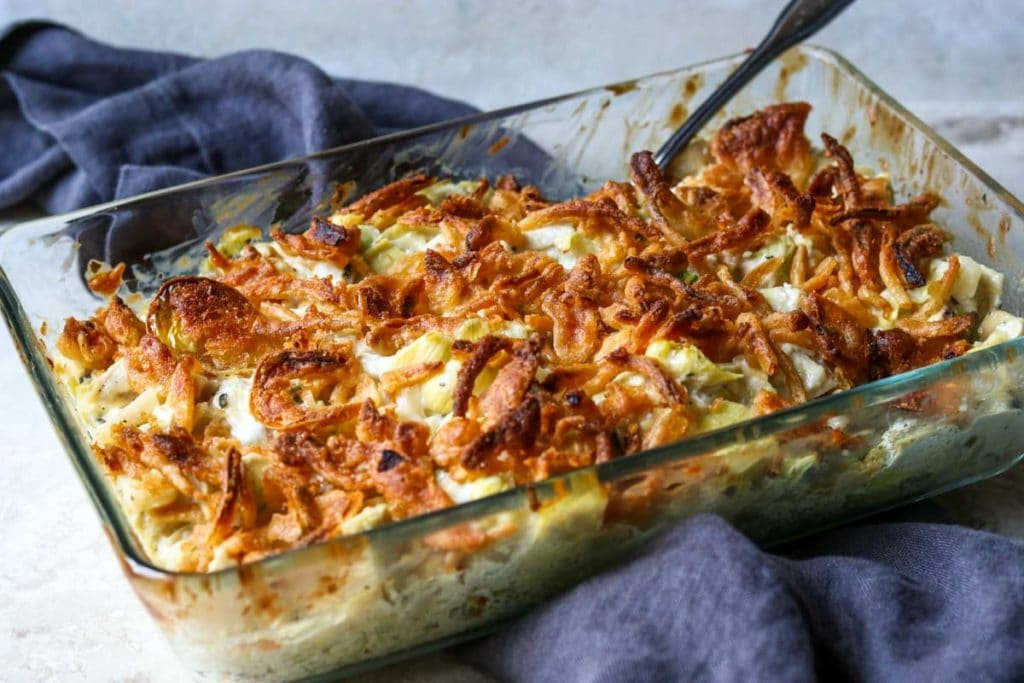 Baking dish of Hot Artichoke Chicken Salad topped with french fried onions, sitting on top of a blue grey towel