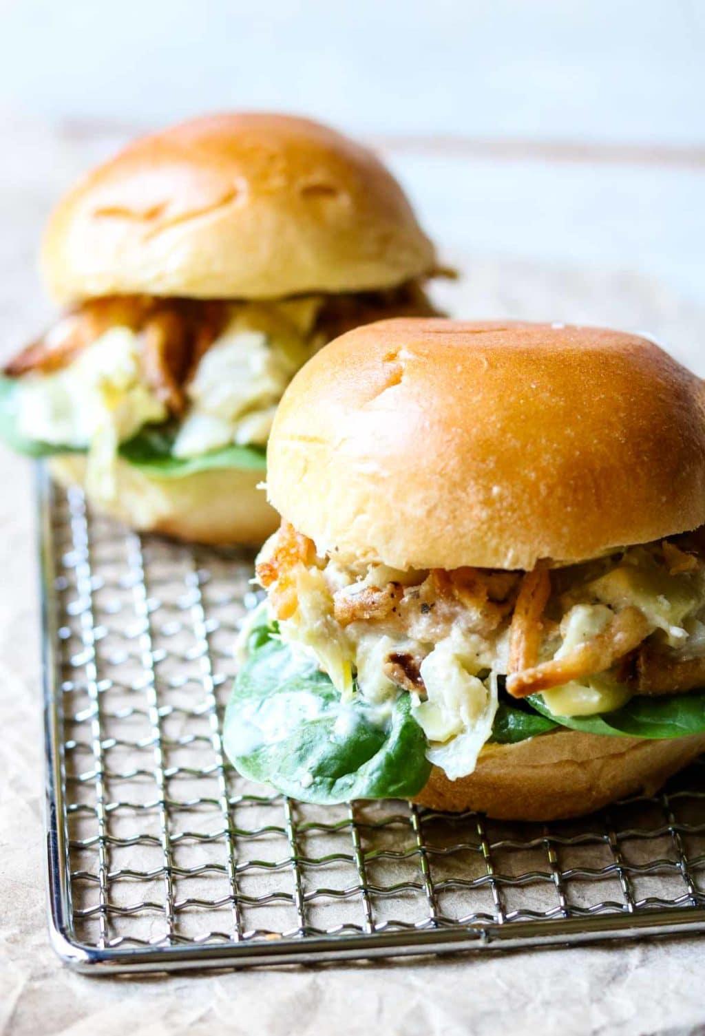 Two Chicken Salad Sandwiches on brioche rolls sitting on a silver grate