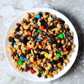 a white bowl full of trail mix that has M&M's in it