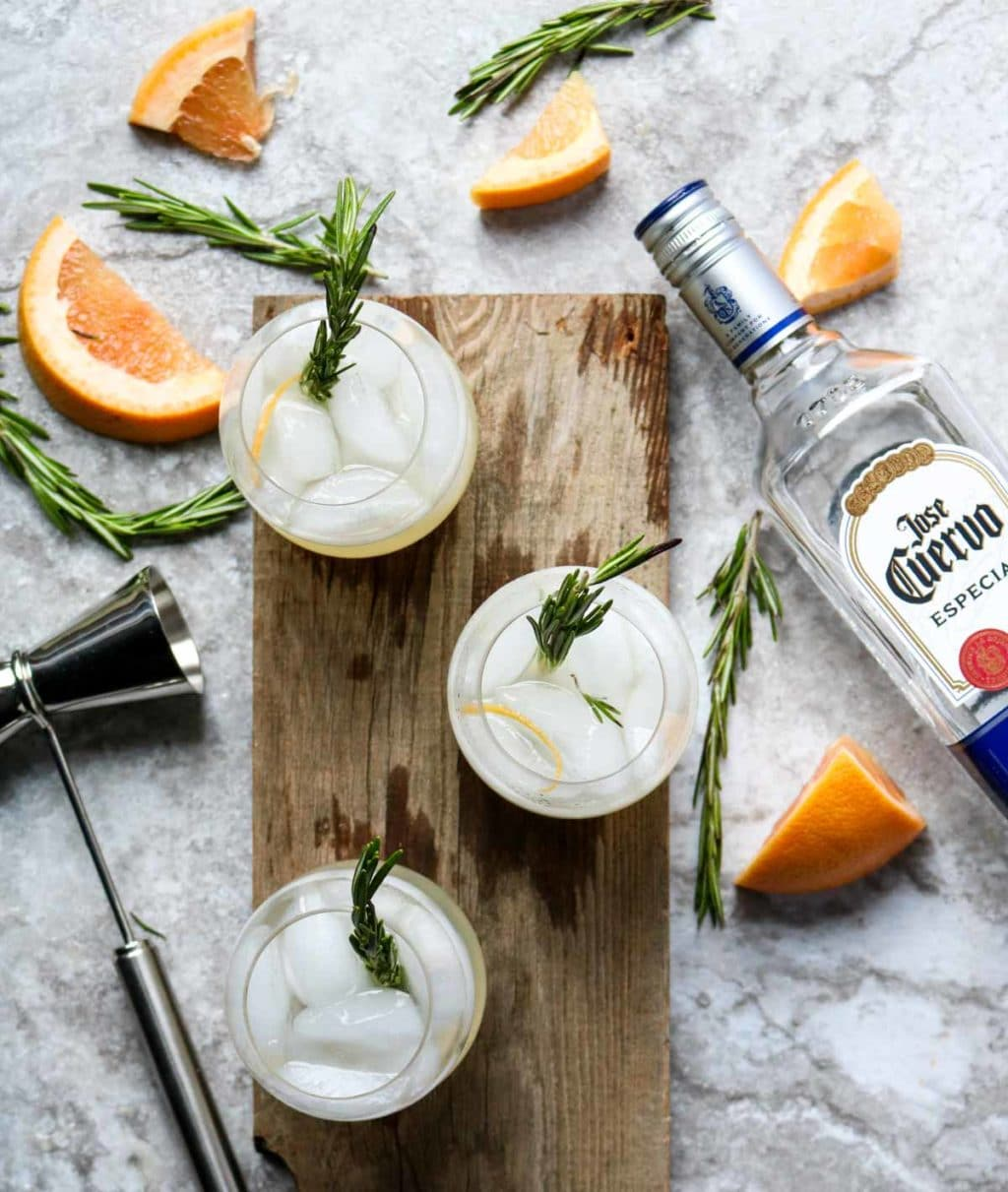 three glass of Rosemary Paloma on a board with a bottle of Jose Cuervo to the side