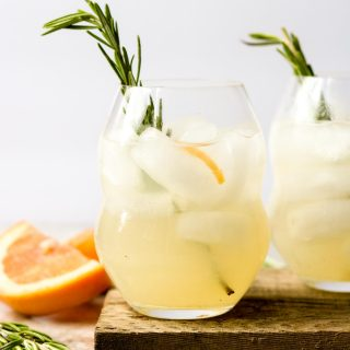 two glasses full of paloma cocktail garnished with rosemary